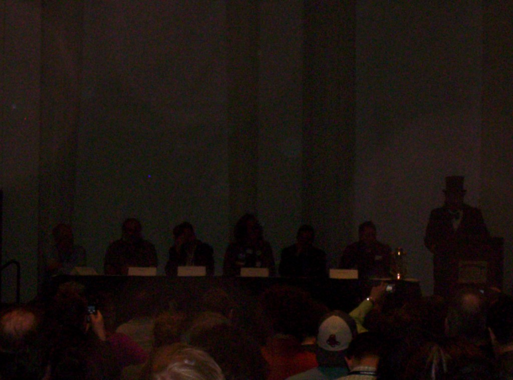 The interactive fiction panelists are pitch black. You are likely to be sorry for botching this photo. Panelists from left to right: Blurry Lebling, Blurry Woods, Blurry Moriarty, Blurry Plotkin, Blurry Montfort, Blurry Meretzky, and Sir Topham Hatt.